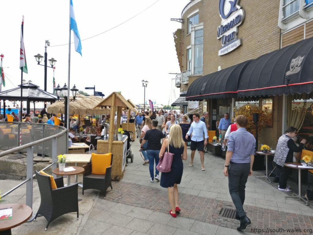 People walking past restaurants in Cardiff Bay
