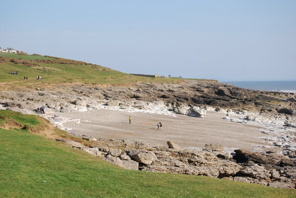 View of the coastal path at Ogmore showing a sandy beach and rocks.